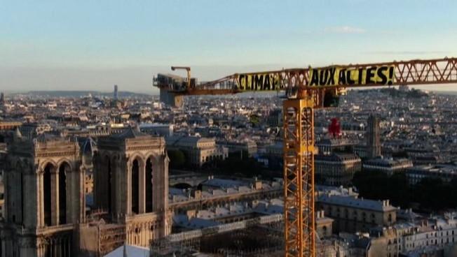 Greenpeace in azione su una gru davanti Notre Dame: Macron agisci